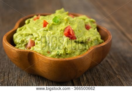 Close up of a bowl of traditional mexican guacamole  on a wooden background