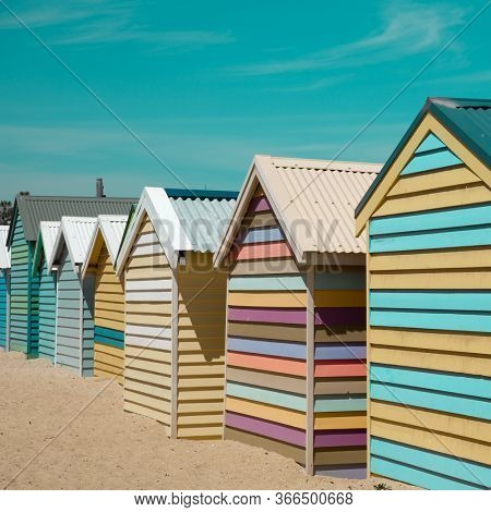 Vintage little beach house in a row in pastel colours and turquoise sky