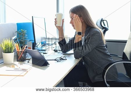 Image Of Business Woman Looking Tired While Sitting At Her Working Place And Holding Paper Cup In Ha