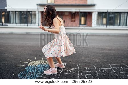 Image Of Cute Little Girl Playing Hopscotch On Playground Outdoors. Pretty Child Plays Next To The H
