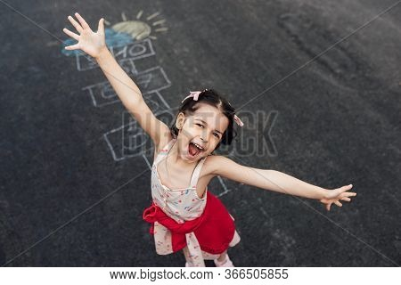 Above View Image Of Happy Little Girl Playing Hopscotch On Playground Outdoors. Child Feels Happy Du