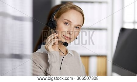 Friendly Businesswoman Talking By Headset In Office. Call Center And Diverse People Group In Busines