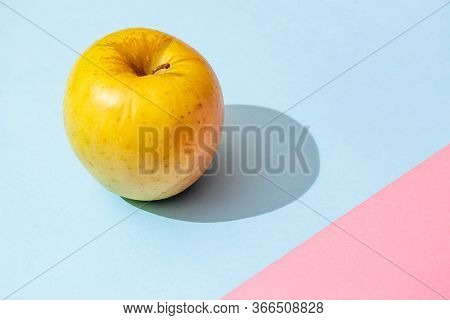 Yellow Apple On Pink Blue Background With Hard Shadow