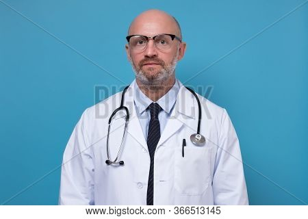 Serious Middle Aged Doctor In Scrubs And Labcoat With Stethoscope Closeup