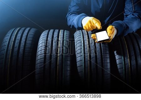 New Tires Selection Concept With Worker Hands With Empty Smartphone Screen And Set Of New Tires.