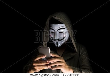 Bangkok, Thailand - May 6, 2018 : A Hacker Wears A Mask Wearing A Robe. Using Smartphone Theft And A