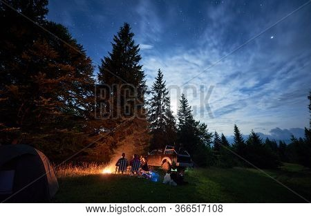 Group Of Travelers Sitting Near Bonfire In Forest With Tall Coniferous Trees, Car And Camp Tent Unde