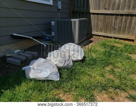 Pile of filty trash bags in back yard of residential home.