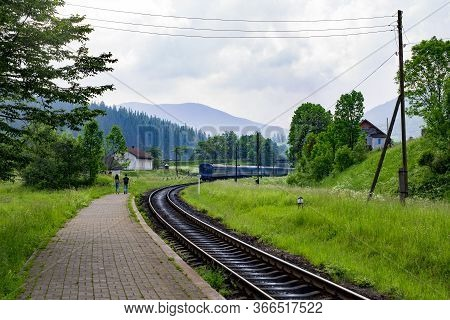 A Guy And A Girl Go Hand In Hand On The Platform After The Outgoing Train In A Mountain Village. Mou