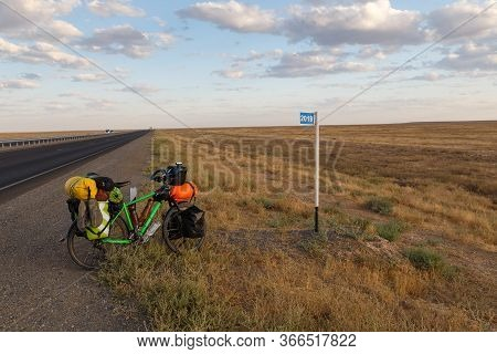 Bicycle For A Traveler Stands On The Road Near A Kilometer Sign 2019, Kazakhstan.