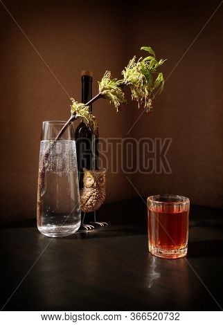 Still Life With Flowering Twig Of Ash-tree With Young Leaves In A Glass Vase, Small Toy Owl, Black B
