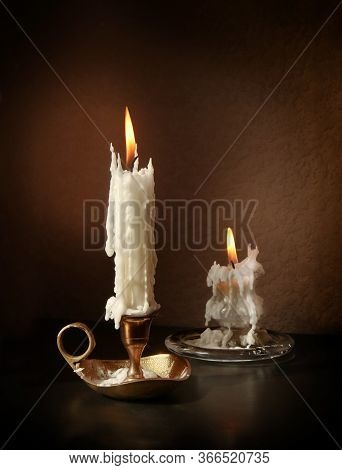 Still Life With Two Vintage Candlesticks With Burning Candles Against Low Key Background With Space