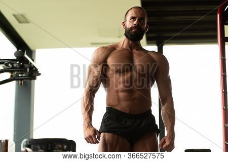 Muscular Man Flexing Muscles In Gym