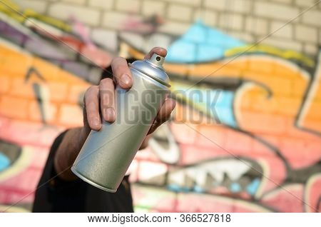 Young Graffiti Artist Aims His Spray Can On Background Of Colorful Graffiti In Pink Tones On Brick W