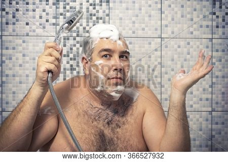 A 40-year-old Man In A Foam Is Standing In The Bathtub Holding A Shower In His Hand, Water Is Not Po