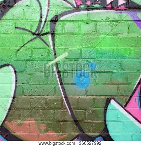 Abstract Colorful Fragment Of Graffiti Paintings On Old Brick Wall In Green Colors. Street Art Compo