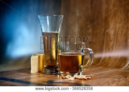 A Glass And A Mug Of Tasty Beer Stand On A Brown Background With Cheese And Nuts. Fragrant Beer Lit