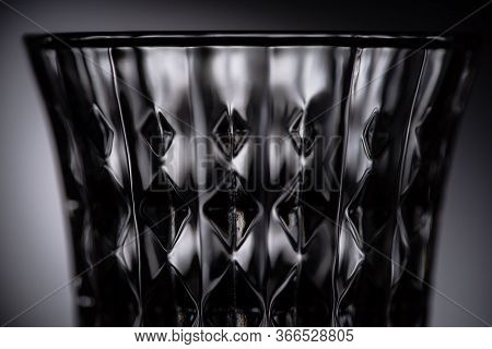 Close Up View Of Empty Faceted Shot Glass On Dark Background