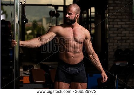 Muscular Man Stretches In A Gym And Flexing Muscles - Muscular Athletic Bodybuilder Fitness Model