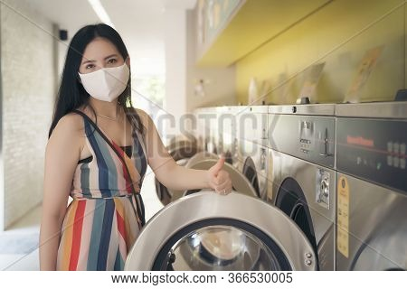 Beautiful Woman With Mask Doing Laundry At Laundromat Shop.