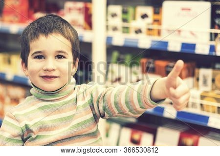 Happy Boy 4 Years In A Supermarket On The Background Of Shelves With Chocolate. The Boy Showed That
