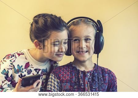 Two Little Happy Girls Together Listening To Music. Two Little Girls Laughing While Listening To Mus