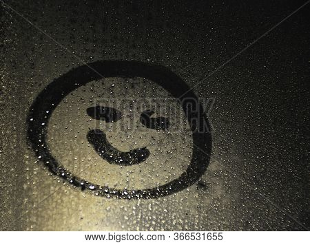 Smiling Smile Painted On Wet Glass. Behind The Glass A Dark Background. Smile Is A Symbol Of Friendl