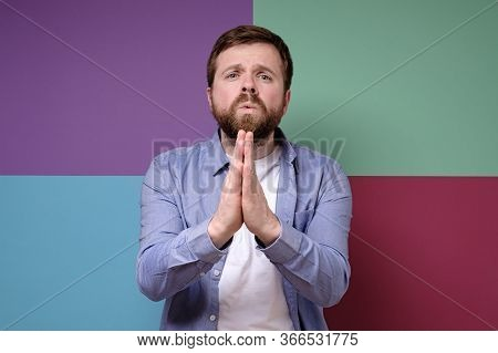 Cute, Caucasian Man With A Pleading Expression On Face Clasped Hands And Looks With Pitiful Eyes.