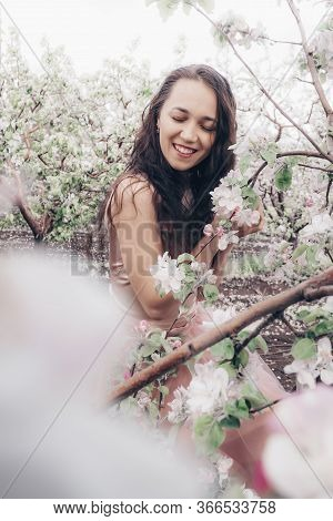 Girl With A Blossoming Apple Tree. Beautiful Smiling Woman Closing Her Eyes With A Branch Of A Bloss