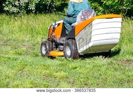 The Gardener Mows Green Grass On The Lawn With A Professional Tractor Lawn Mower On A Clear Sunny Da