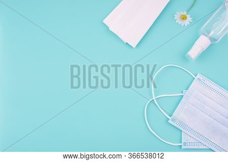 Surgical Face Masks, Hand Sanitizer Spray, Antibacterial Napkins And Chamomile Flower On A Light Blu