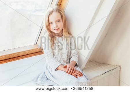 Stay Home Stay Safe. Little Cute Sweet Smiling Girl In White Dress Sitting On Window Sill In Bright