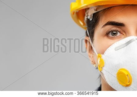 profession, construction and building - close up of face of female worker or builder in helmet and respirator mask over grey background