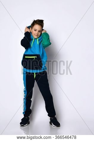 Sly Active Smiling Kid In Modern Cotton Tracksuit With Cute Hairdo Putting Hood Over His Head. Styli