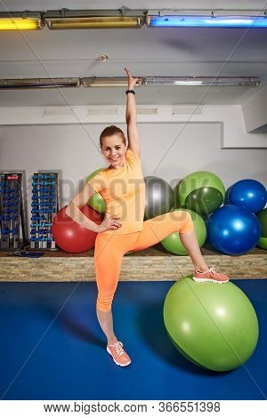 Slim Athletic Young Woman In Sportswear Does Exercises Using Fitboll In Fitness Club. Female Home Wo