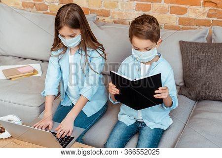 Siblings In Medical Masks E-learning In Living Room