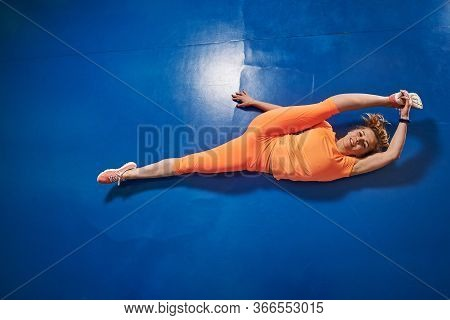 Slim Athletic Young Woman In Sportwear Does Sport Stretching Exercises In Fitness Club Gym.