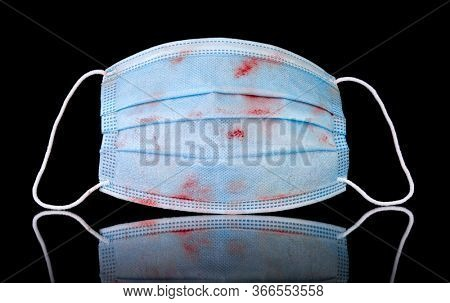 Medical face mask of a doctor or nurse, worn, dirty, and bloody on black.