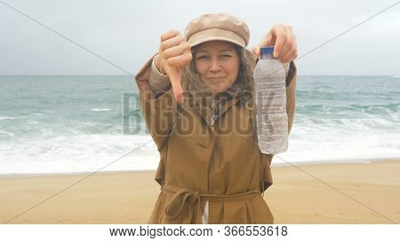 Blonde Girl Holds Empty Thrown Bottle And Thumbs Down Showing Discontent To Shameless People On Beac