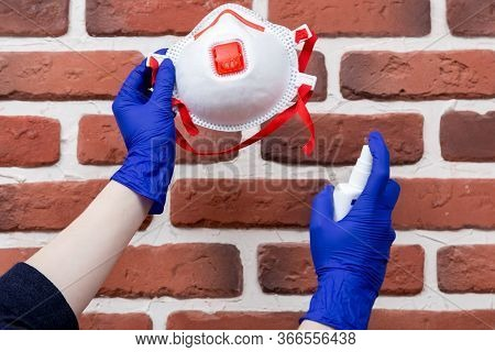Woman In Latex Gloves Is Cleaning Her Disposal Respirator Using Sanitizer. Reusing Of Respirators In