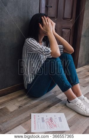 Woman Covering Face Near Document With Foreclosure And Final Notice Lettering On Floor Near Wall In