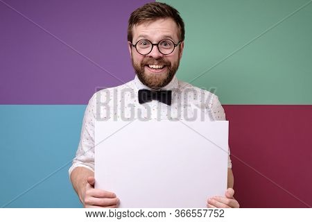 Cute, Weird Salesman Is Holding An Empty White Board With Copy Space And Is Smiling Friendly. Season