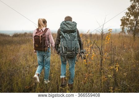 Hiking In Autumn Nature, Couple Of Backpackers Makes Their Way Across The Field, Rear View Of Man An