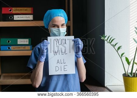 Poor Prediction Or Outlook From Doctor. Sarcastically Smiling Nurse In Protective Uniform Holds A Pa