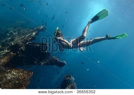Mladá žena prozkoumat vrak lodi na blokování dechu. Tulamben, Indonésie
