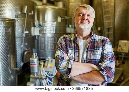 Man as a brewer or winemaker in a brewery or winery in front of a fermentation tank