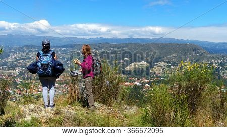 Azuay, Ecuador - December 2, 2018: Two Women Hikers аrе On The Top Of Hill And Look At The Valley. A