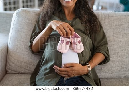African pregnant woman holding small shoes. Close up of baby bump with pink little baby shoes on it. Close up hands of young lovely pregnant woman holding baby booties on belly for her future daughter