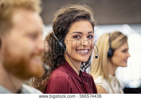 Portrait of confident woman working in a call center while looking at camera. Customer care rappresentative working with team in office sitting in a row. Support online with latin call center agent.