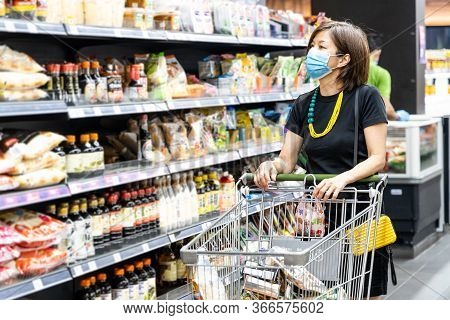 Asian Woman Shopping Groceries In Supermarket With Protective Face Mask As New Normal Requirement In